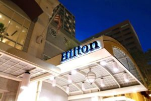 an upward view of a building facade at night, with the word Hilton lit up