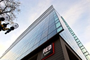 a view from below of a tall hotel stretching up into the sky with the word Red on the side